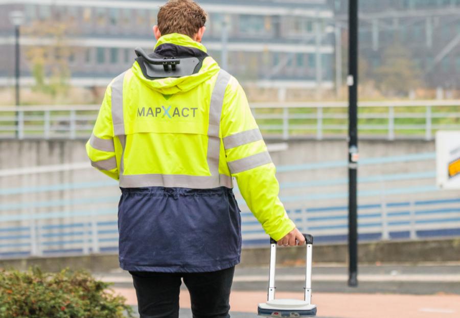Revisiemeting van man met gele jas en MapXact logo